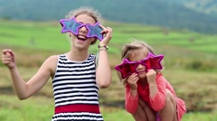 Cheerful girl in big glasses in the shape of stars looks at the camera and dance Stock Footage