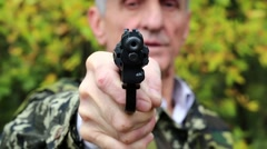 Man with black revolver in hand looks at the camera Stock Footage