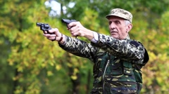 Soldier in military uniform shoots from two pneumatic handguns Stock Footage