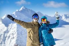 Happy young couple snowboarders on the background high mountains on the winte Stock Photos