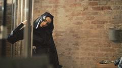 Devilish female enchantress in the black coat posing near the lattices 4K Stock Footage