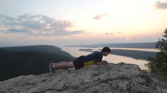Man doing exercise at the press on top of the mountain Stock Footage