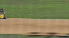 A baseball player drives a tractor to prepare the infield a game, slow motion. Stock Footage