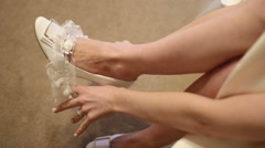 Bride is putting on a wedding garter Stock Footage