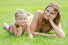 Young mother and five year old daughter lying on green grass and looking to t Stock Photos