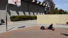 Establishing master shot of men playing two-on-two pick up basketball on a playg Stock Footage