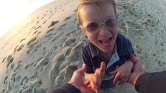 POV of a father holding his son's hands and spinning him around on the beach at Stock Footage