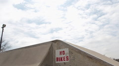 A young man rides his BMX bicycle and does a trick despite a sign that says 'No Stock Footage