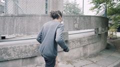 4K Graffiti artist with breathing mask & spray can walking through urban area Stock Footage