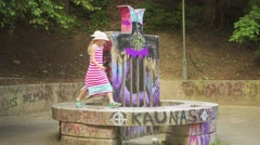 Two little girls playing on monument in Kaunas Stock Footage