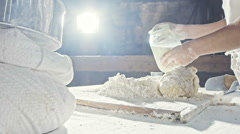 A young baker adds a milk into the flour Stock Footage