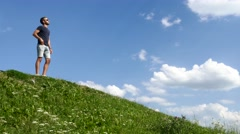 Handsome young man wearing jeans standing on top of a hill - reaching success Stock Footage