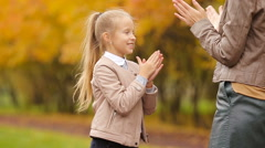 Happy mom and cute girl having fun fall day in autumn park outdoors Stock Footage