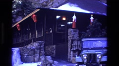 1969: red lantern building close to the base of a large rock on a snowy day Stock Footage