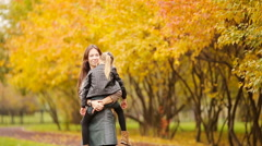 Adorable little girl with mother enjoy fall day in autumn park outdoors Stock Footage