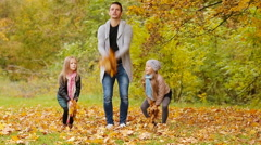 Happy family having fun and throwing leaves around on an autumn day outdoors Stock Footage