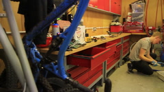 Panning shot of a man working on his mountain bike in a workshop. Stock Footage