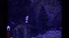 1969: a santa claus decorating the top of a shed's roof outside COLORADO Stock Footage