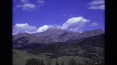 1969: majestic panorama of rocky mountain landscape with summer fields under Stock Footage
