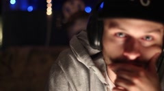 Portrait of a young man with a hat, beard, headphones, and hoodie sweatshirt, sl Stock Footage