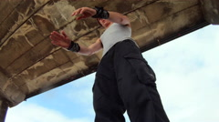 A man does a parkour freerunning backflip under a pier on the beach. Stock Footage