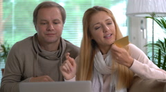 Couple doing online purchases uses gold credit card. Stock Footage