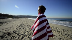 SLO MO TS WS of a man on the beach with an American Flag and gold medal. Stock Footage