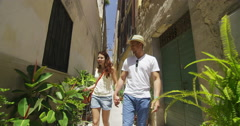 4K Attractive couple on vacation walking through narrow alley with lots of plant Stock Footage