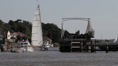 Sailing & motor cruisers pass through swing bridge on Norfolk Broads Stock Footage