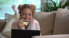 A young woman uses a golden credit card online lying on the couch. Dolly shot. Stock Footage