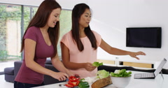 4k, Two young women following a recipe on a laptop while chopping vegetables. Stock Footage