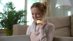 A young woman uses a golden credit card online sitting on the floor. Slow motion Stock Footage