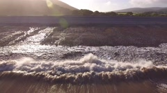 Titling low aerial shot of waves crashing onto the beach. Stock Footage