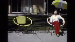 1965: lady sitting in a chair and a man sits beside her CENTRAL COAST CALIFORNIA Stock Footage