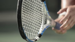 Extreme close-up of a male tennis player holding and spinnig a tennis racquet. Stock Footage
