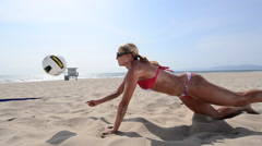A dolly tracking panning shot of a female beach volleyball player diving for the Stock Footage