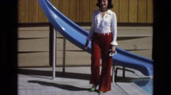 1965: woman wearing red belle bottom pants walks past blue slide CENTRAL COAST Stock Footage