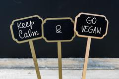 Keep Calm and Go Vegan message written with chalk on mini blackboard labels Stock Photos