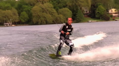 A man doing a jump and board grab while wakeboarding on a lake, slow motion. Stock Footage