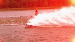 A man doing a jump and flip while wakeboarding on a lake, slow motion. Stock Footage