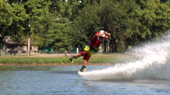 A wakeboarder crashes in the water while trying to do a risky trick, slow motion Stock Footage