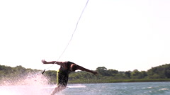 A waterskier crashes in the water while trying to do a risky trick, slow motion. Stock Footage