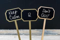 Keep Calm and Do Not Quit message written with chalk on mini blackboard label Stock Photos