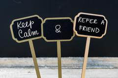 Keep Calm and Refer A Friend message written with chalk on mini blackboard la Stock Photos