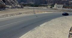 Car takes off on coastal road Musandam Governate of Oman Stock Footage
