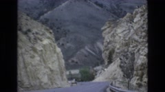 1965: a road or highway cutting through the mountains as seen from a vehicle Stock Footage