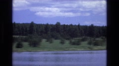 1966: ridge of trees behind a wide river with snow covered mountain range  Stock Footage