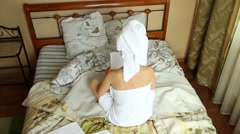 Seductive girl dressed in towel with neat body sitting on a bed and reading Stock Footage