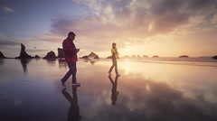 Mature, middle aged couple strolling beach using cellphones Stock Footage