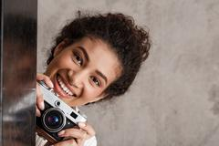 Attractive female photographer holding camera, looking out over beige background Stock Photos